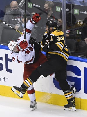 Boston's Patrice Bergeron hits Carolina's Jordan Martinook during the third period of Wednesday's game.