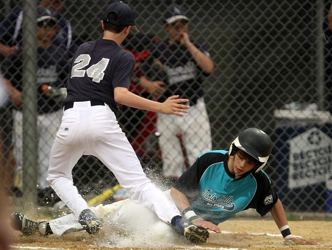 Eli Rife of Tinton Falls collides with Lincroft pitcher Chris Marino while scoring during the first inning in the District 19 Little League semi-final, Wednesday, July 9, 2014, at Hockhockson Park in Tinton Falls, NJ.  Photo by Jason Towlen