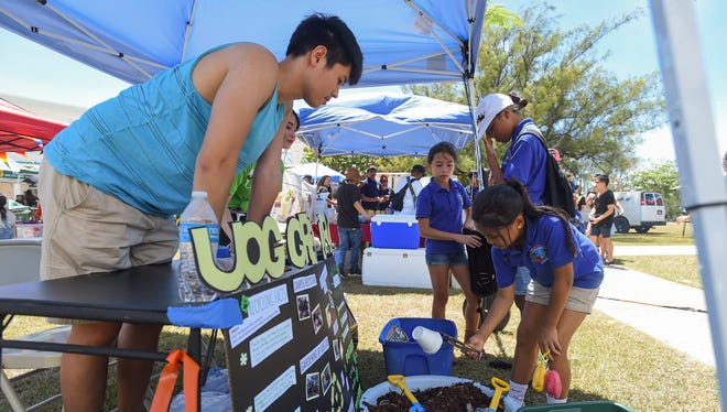 """Inarajan Elementary School students participate in a recyclable sorting activity at the """"UOG Green Army"""" booth during the University of Guam's 50th Charter Day in Mangilao on March 13, 2018."""