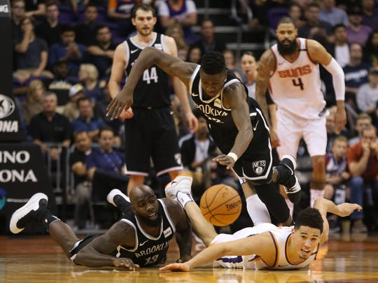 Suns' Devin Booker (right) and Nets' Quincy Acy dive for a loose ball as Chris LeVert hurdles them during the second half of Monday's loss.