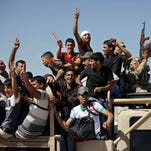 Men flash victory signs as they leave the main recruiting center to join the Iraqi army in Baghdad on June 17 after authorities urged Iraqis to help battle insurgents.