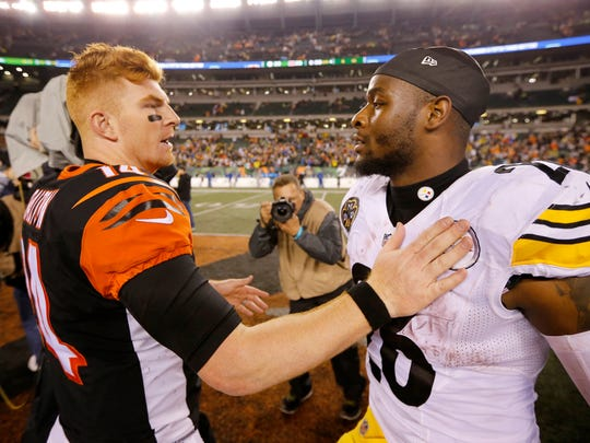Cincinnati Bengals quarterback Andy Dalton (14) and Pittsburgh Steelers running back Le'Veon Bell (26) hug after the NFL Week 13 game between the Cincinnati Bengals and the Pittsburgh Steelers at Paul Brown Stadium in downtown Cincinnati on Tuesday, Dec. 5, 2017. The Bengals gave up a 17-3 halftime lead to lose 23-20 on a last-second field goal.