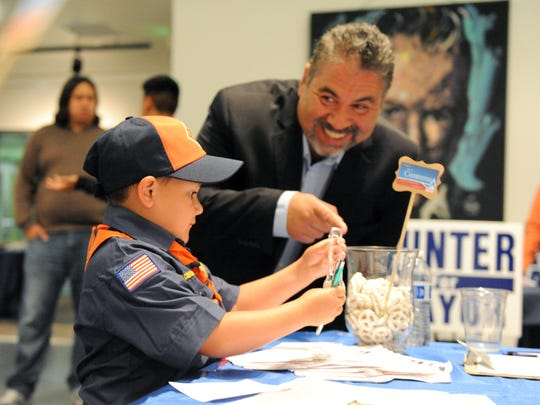District 1 candidate Brian Contreras Sr. tries to woo a young voter, Jacob Torrez, 6.