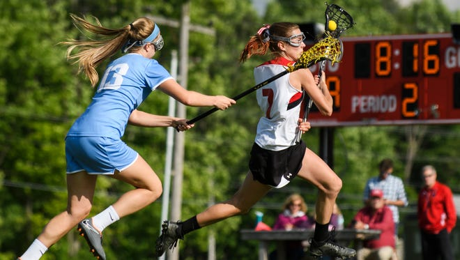 CVU's Cate Noel (7) runs past South Burlington's Caroline Desautels (13) with the ball during the girls lacrosse game between the South Burlington Wolves and the Champlain Valley Union Redhawks at CVU High School on Wednesday afternoon June 6, 2018 in Hinesburg.