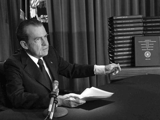 In this April 29, 1974, file photo, President Richard M. Nixon points to the transcripts of the White House tapes after he announced during a nationally-televised speech that he would turn over the transcripts to House impeachment investigators, in Washington.  (AP Photo/File)