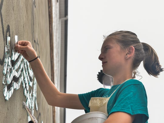 Rylee Strayer glues a piece of mirror to the mural