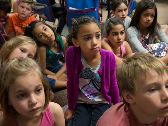 Lauran Clark (center) and her second-grade classmates listen as their teacher reads them a story, Monday, April 21, 2014, at Norterra Canyon School in Phoenix.