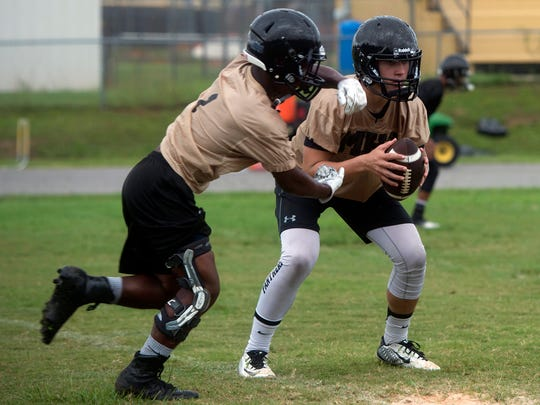 Milton High School's Aubrey Williams, right, takes a few reps as quarterback during preseason practice Tuesday morning. Area high school teams have returned to preseason training schedules in preparation for the 2016 season opener later this month.
