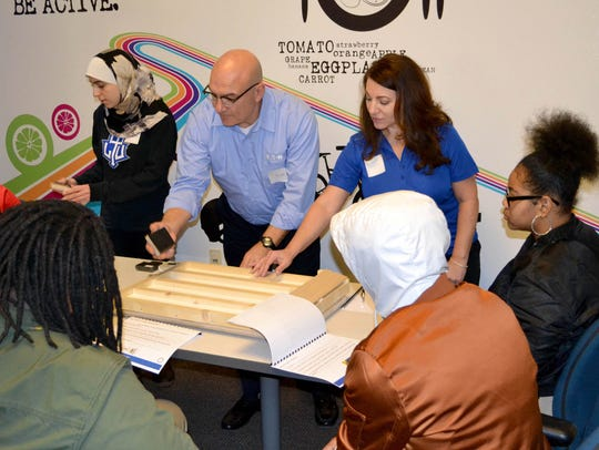 """From left, Nada Saghir, Eaton intern from Lawrence Technological University; Larry Bennett, director of vehicle technology and innovation; and Deborah Kullman, VP of business development and marketing in Eaton's Vehicle Group, provide a """"hands-on"""" lesson on the coefficient of friction and friction forces to Detroit Collegiate Prep"""