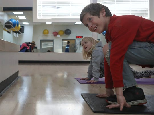 Chuck Ballou, right, 8, and his sister Faith, 6, do yoga and Pilates Tuesday during home school physical education at the Shasta Family YMCA.