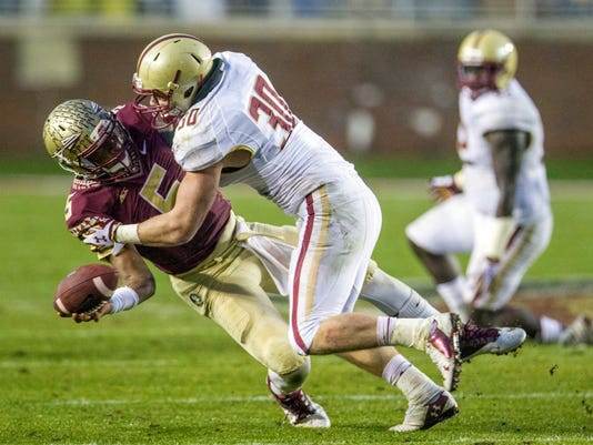Florida State quarterback Jameis Winston, left, passes as he is hit by Boston College linebacker Mike Strizak in the second half of an NCAA college football game in Tallahassee, Fla., Saturday, Nov. 22, 2014. Florida State won 20-17.  (AP Photo/Mark Wallheiser)