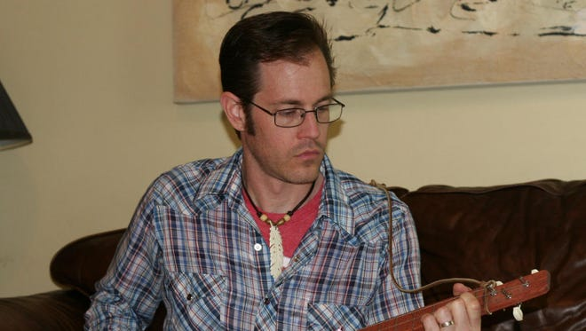 Dustin Michael Headrick, owner of Nashville Picks, practices playing the guitar while using one of his handcrafted picks.