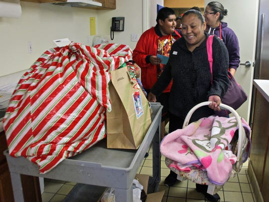 Mecca resident Reyna Perez prepares to depart Las Palmas Community Church in Indio after picking up clothes, toys and meals for Christmas.