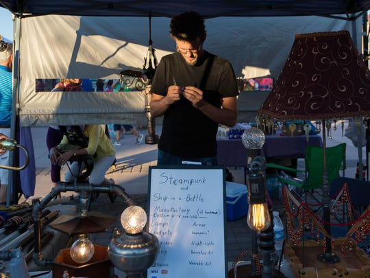 "Zach Carpenter, works on a piece of custom jewelry at his booth ""Zach B. Nimble"" where he sells hand made steampunk accessories and jewelry. Wednesday, June 14, 2017 at the first evening farmers market of the year in the Plaza de Las Cruces,"