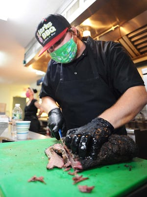 In this Thursday, July 2, 2020, file photo, Chris DePalma, co-owner of 2 Jerks BBQ restaurant, carves up some BBQ at the Easton Country Club.
