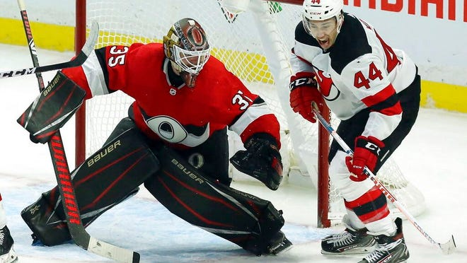 New Jersey Devils left wing Miles Wood (44) and Ottawa Senators goaltender Marcus Hogberg (35) keep their eyes on a loose puck during third period NHL hockey action in Ottawa on Monday, Jan. 27, 2020.