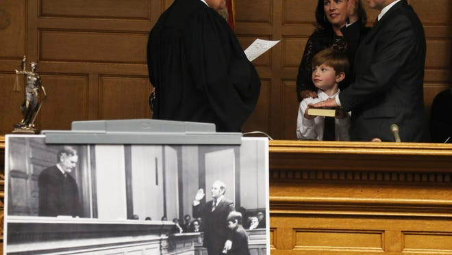 An old black-and-white photo in front of the bench depicts Thomas Rumana, Scott's father, being sworn in as a judge in 1972 as Scott held the Bible. On Tuesday, Thomas Rumana swore in son Scott as Tommy Rumana, Scott's son, held the Bible. Scott's wife, Laura, also took part.