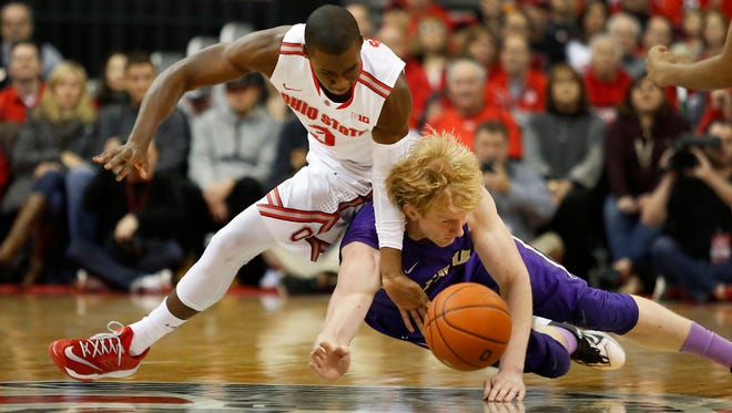 Ohio State guard Shannon Scott dives for the loose ball with James Madison forward Paulius Satkus during the first half Friday at Value City Arena.