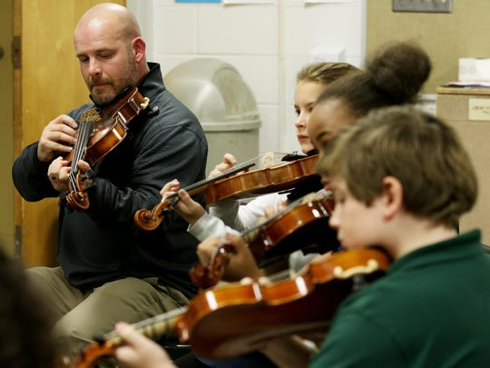 Day practices the viola with fifth-graders.