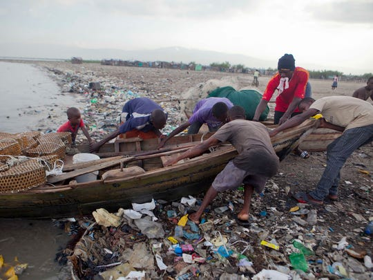 Fishermen remove their wooden boat from the sea as a precaution against Hurricane Irma, in the seaside slum of Port-au-Prince, Haiti, Sept. 6, 2017.