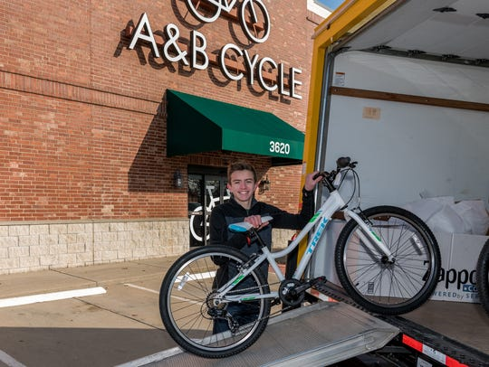 Garrett Litherland, a junior at Greenwood Laboratory School, helps load new, custom-built bicycles into a moving truck. The bicycles, 46 in all, were donated to children of men and women serving at Whiteman Air Force Base.