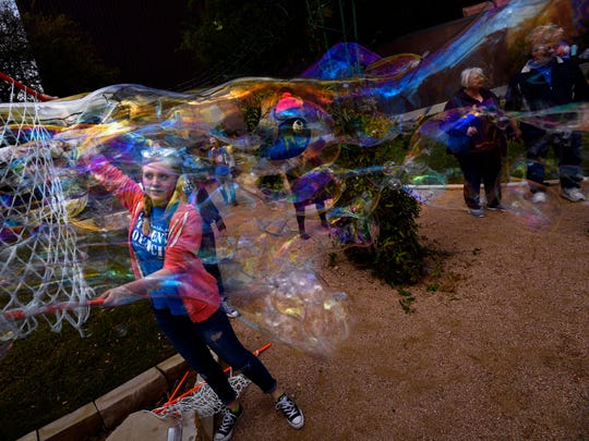 Madi Melbourne, storybook characters, and visitors to the Adamson-Spalding Storybook Garden are distorted seen through the bubbles coming out of Melbourne's net Saturday during Big Day Downtown in Abilene.