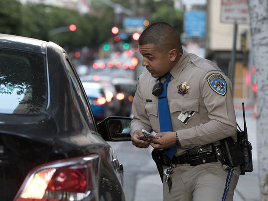 Highway Patrol Officer Benjamin Gomez speaks with a motorist during a traffic stop in downtown Los Angeles, California on Friday, April 13, 2018.