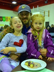 Bill Morningstar enjoys breakfast with his daughters, second grader Arie and 4-year-old Nollie, at Buckingham Elementary School's Donuts with Dads day Wednesday, March 23.