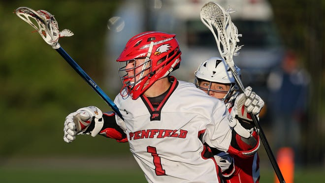 Penfield's Max Spaan (1) is tied up around the goal by Fairport's Cameron Krug.