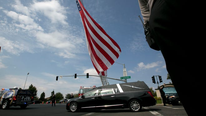 The hearse carrying the body of Sacramento County Deputy Sheriff Robert French passes under a large American flag after funeral services at the Bayside at Adventure Church on Thursday in Roseville.