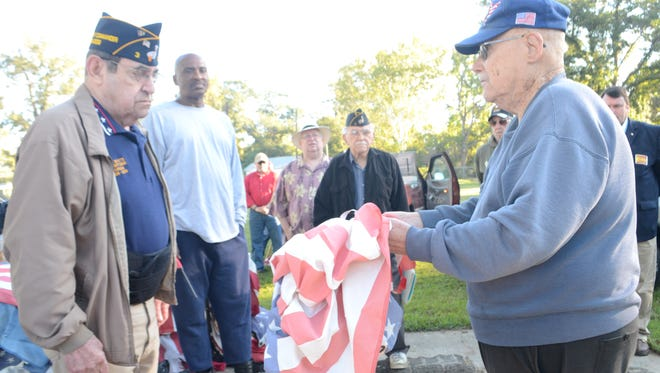 George Simmons Jr. American Legion Post 3 adjutant Harold Teal (right), holds an American flag out for first vice commander Archie Boyette to inspect and give the order to retire the flag. The post held a flag retirement ceremony Saturday. The post holds two ceremonies a year, one in the spring and one in the fall. Besides the Boys Scouts of America, American Legion Post 3 is the only organization in Central Louisiana that retires unserviceable flags. An old mailbox sits in front of the post headquarters on Bayou Rapides where unserviceable flags can be placed so they can be retired properly.
