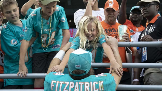 Dolphins quarterback Ryan Fitzpatrick greets his children after a 38-35 overtime win against the Cincinnati Bengals at Hard Rock Stadium.