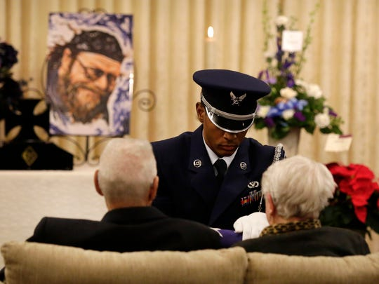 Senior Airman Malcolm Hamilton presents a flag to the family of Michael L. Funk during funeral services with full military honors in Oshkosh on Dec. 13. Funk, 60, died Dec. 5 after he was shot at by police.