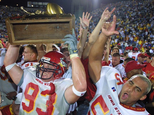 Iowa State's Kyle Knock (93) holds the Cy-Hawk Trophy up in celebration of the Cyclones' 36-31 win against Iowa on Sept. 14, 2002, at Kinnick Stadium in Iowa City. Beau Coleman (55) is also pictured.