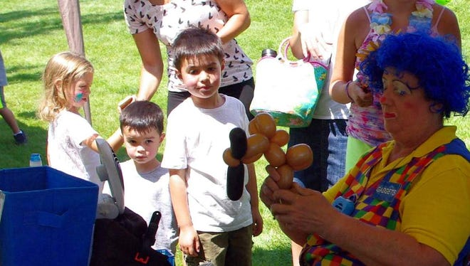 Children wait patiently while the festival's resident clown creates balloon animals.