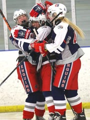 PCS Penguins senior captain Megan Brace (No. 20) is mobbed by jubilant teammates Cathryn VandenBosch (left) and Jessica Marek (No. 40) after Brace scored in the third period Tuesday.
