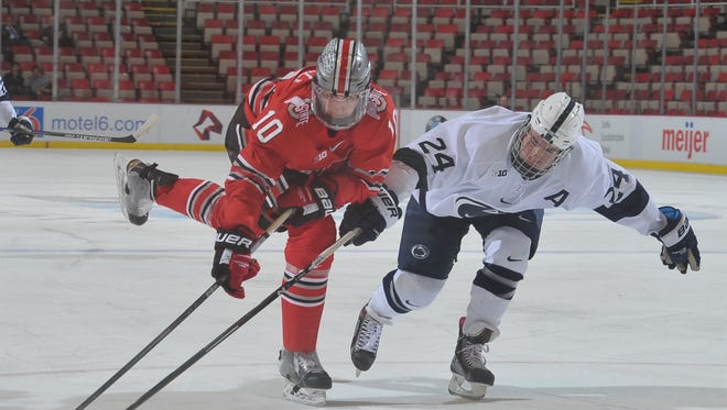 Ohio State's Darik Angeli keeps the puck away from Penn State's Nate Jensen in the second period.