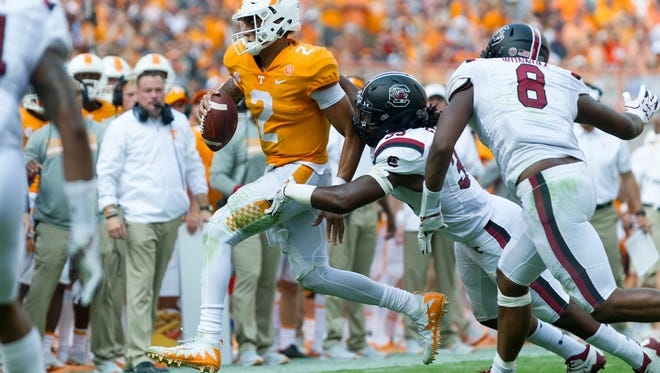 Tennessee quarterback Jarrett Guarantano (2) runs the ball as Tennessee defensive back MaLeik Gatewood (33) tackles him during the Tennessee Volunteers vs South Carolina Gamecocks game at Neyland Stadium in Knoxville, Tennessee on Saturday, October 14, 2017.
