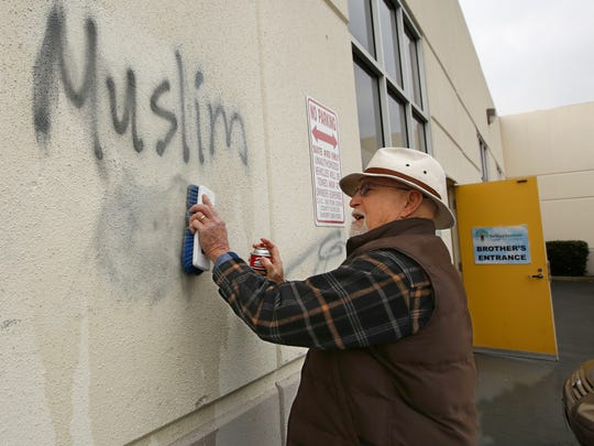 In this Feb. 1, 2017, file photo, Tom Garing cleans up graffiti painted on the side of a mosque in Roseville. A report released by the state auditor says California is underreporting hate crimes to the FBI and largely blames Attorney General Xavier Becerra's state Department of Justice for not requiring local agencies to do a better job.