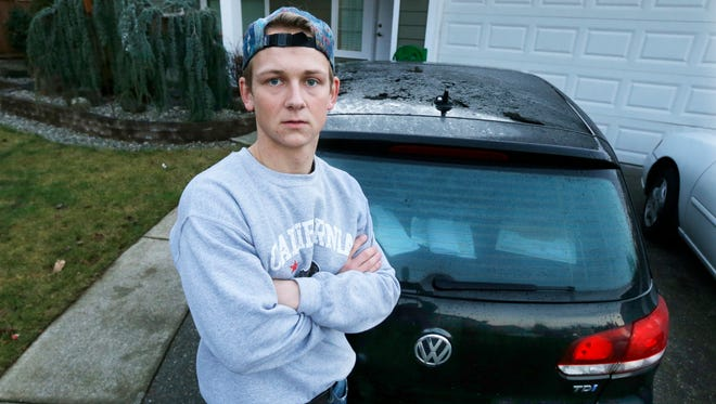 In this Tuesday, Jan. 24, 2017, photo, David Derkach poses for a photo with his Volkswagen Golf, at his home in Federal Way, Wash. Derkach has faced delays in getting Volkswagen to buy back his diesel-engine vehicle following VW's emissions-cheating scandal.