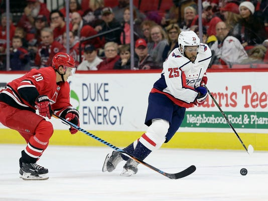 Carolina Hurricanes' Sebastian Aho (20), of Finland, chases Washington Capitals' Devante Smith-Pelly (25) during the first period of an NHL hockey game in Raleigh, N.C., Tuesday, Jan. 2, 2018. (AP Photo/Gerry Broome)