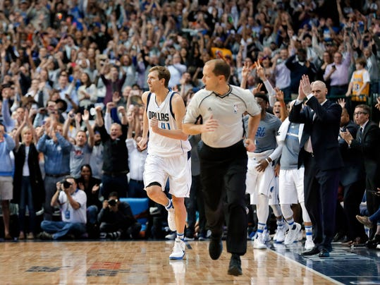 Fans stand and cheer along with Dallas Mavericks head coach Rick Carlisle, right, after Dirk Nowitzki (41) of Germany sunk a basket to reach his 30,000th career point in the first half of an NBA basketball game against the Los Angeles Lakers in Dallas, Tuesday, March 7, 2017. (AP Photo/Tony Gutierrez)