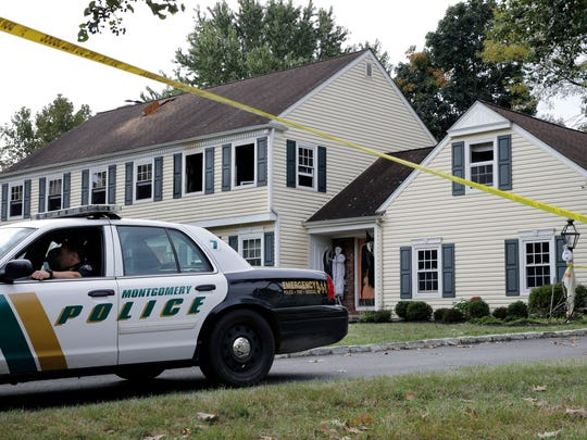 A Montgomery Township police officer sits in front of the Sheridans' Somerset County home on Sept. 29, the day after a fire and violent incident at the couple's home.