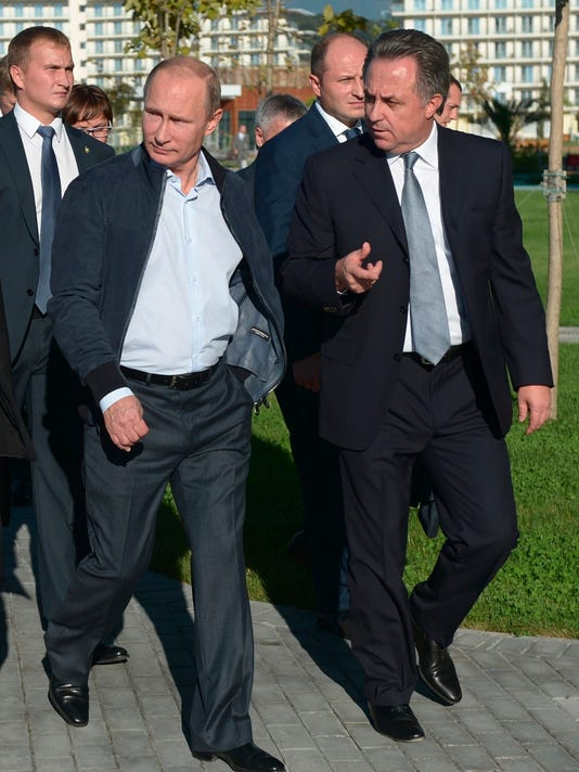 FILE - In this Saturday, Oct. 11, 2014 file pool photo Russian President Vladimir Putin, second left, and Sports Minister Vitaly Mutko, right, visit a sports center in the Black Sea resort of Sochi, Russia. Russian sports minister Vitaly Mutko, who has come under scrutiny in Russia's doping scandal, has been promoted to a deputy prime minister, on Wednesday Oct. 19, 2016. State news agency Tass says President Vladimir Putin approved a proposal by Prime Minister Dmitry Medvedev to appoint Mutko to a deputy premiership in charge of sport, tourism and youth policies. (AP Photo/RIA-Novosti, Alexei Nikolsky, Presidential Press Service, File)