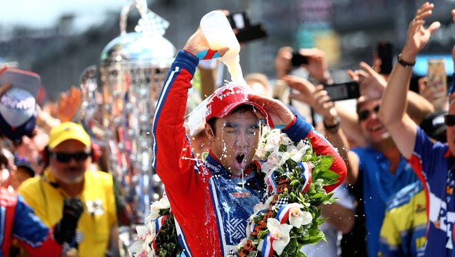 Takuma Sato dumps milk on himself as he celebrates after winning the 101st running of the Indianapolis 500.