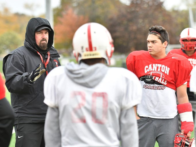 Canton head football coach Tim Baechler, left, gives