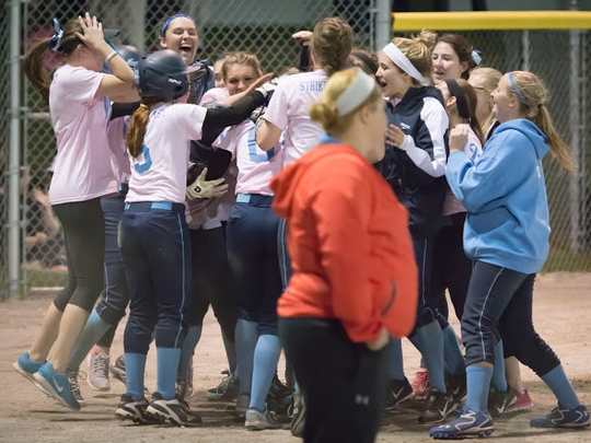 Livonia Stevenson softball players celebrate after Kayce Ziemba's walk-off home run earned them an exciting victory over Livonia Churchill Monday night at Ford Field.