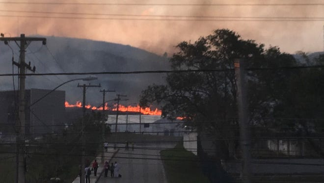 A fire burns roughly 10 miles from the Olympic field hockey venue during the 2016 Summer Olympics in Rio de Janeiro, Brazil, Aug. 15. The fire was near the mountain bike course, but won't affect the race Dr. Peter Lombard will compete in on Sunday.