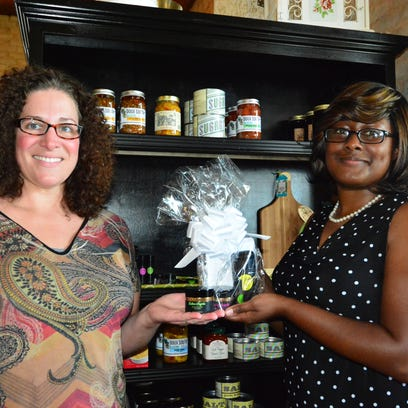 Cristy Ray, left, owner of Foodies Farm Shop in Greer and Rolande Sumner,  founder of Butter Angela skin care products pose with one of the gift packages sold in the store.