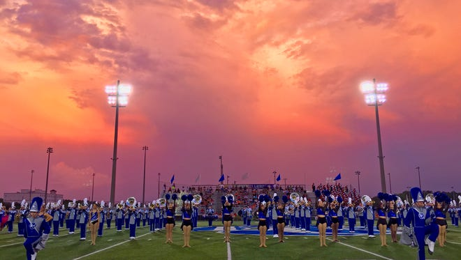 Storm clouds at sunset create beautiful colors as the Barron Collier band performs before the game against Lely at Barron Collier Friday night, September 23, 2016. Photo by Darron R. Silva